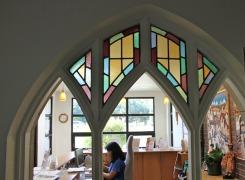 View through retained existing stained glass gothic windows to reception area addition